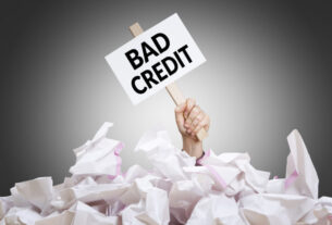 Bad credit placard in hand with crumpled paper pile. Concept of bad financial situation.